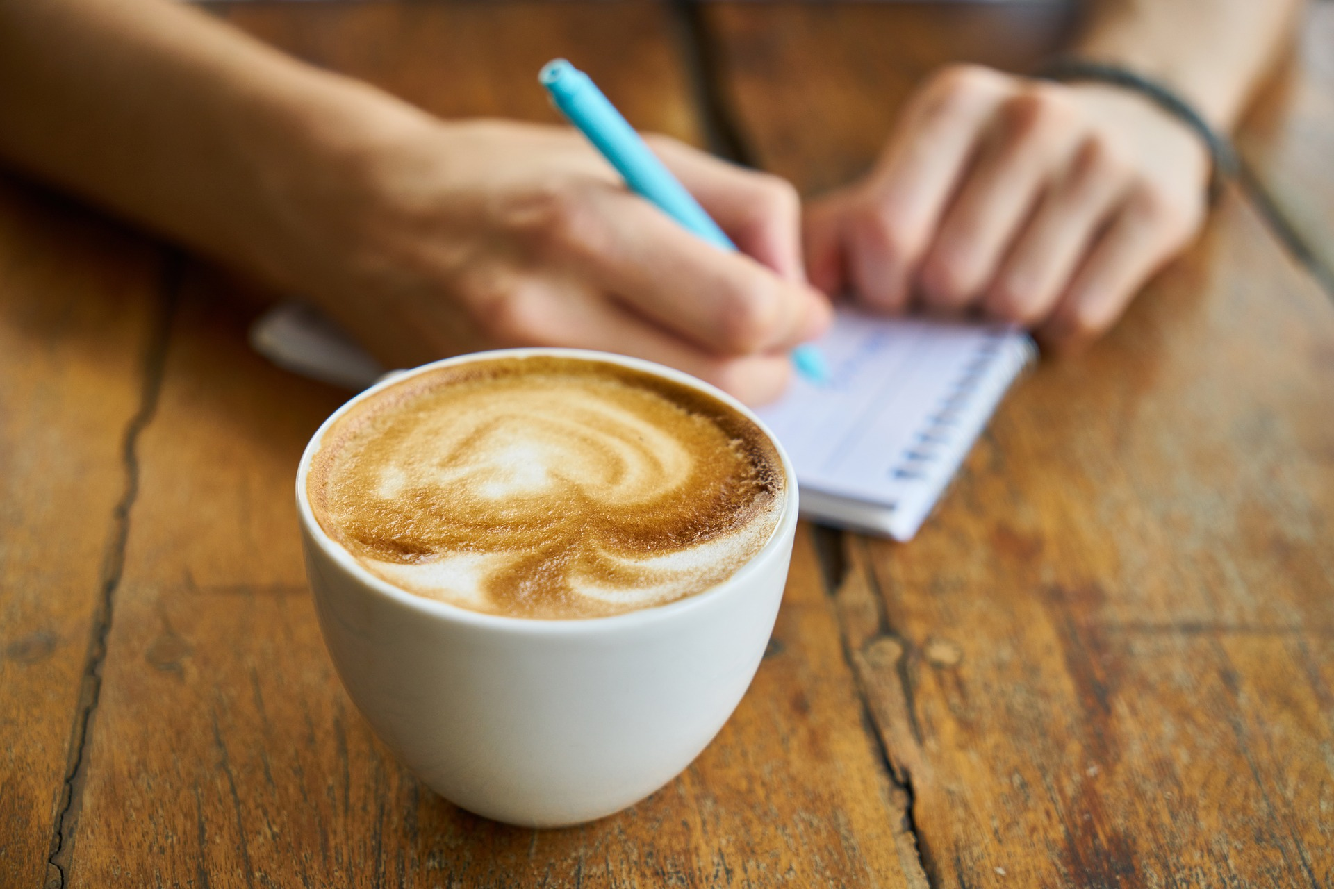 Eine Person schreibt notiezen auf einen Blog, im vordergrund eine Tassekaffee
