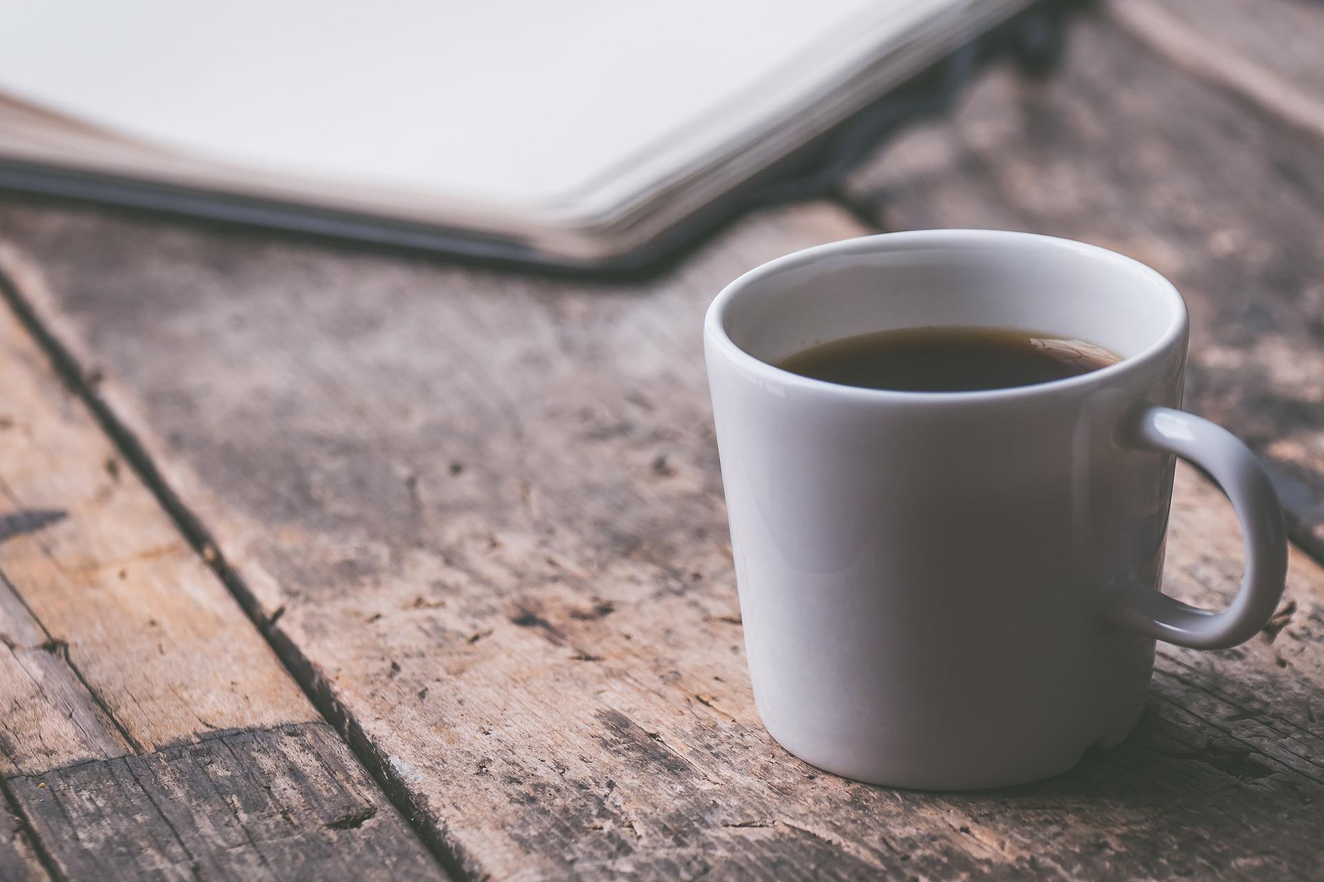 Tasse Kaffee und im Hintergrund ein Schreibblock auf Holztisch